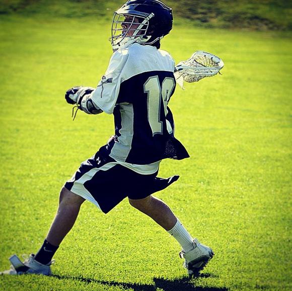 Teenager playing lacrosse wearing a SquadLocker uniform