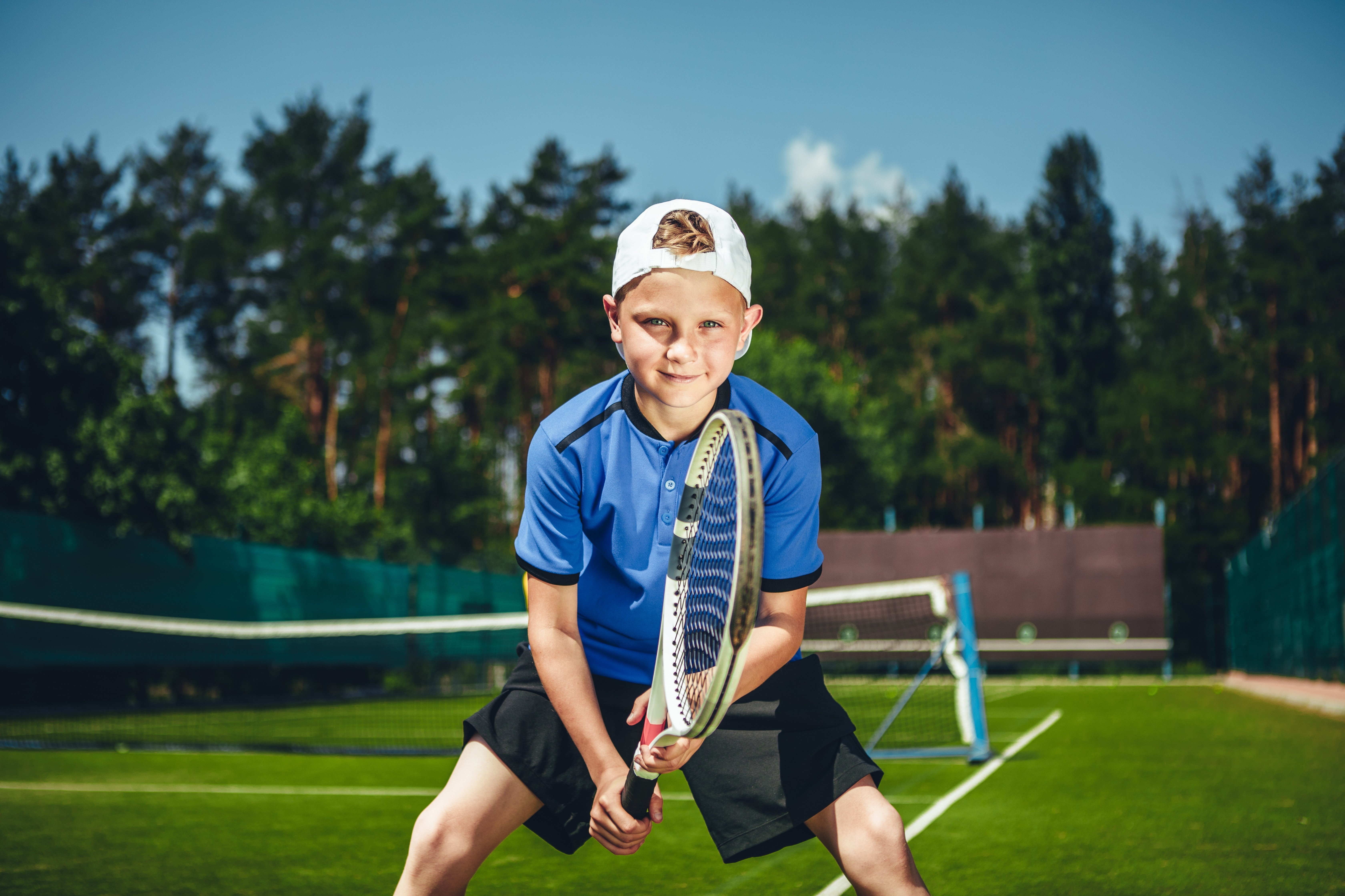 Proud/happy child holding tennis racket on green tennis field