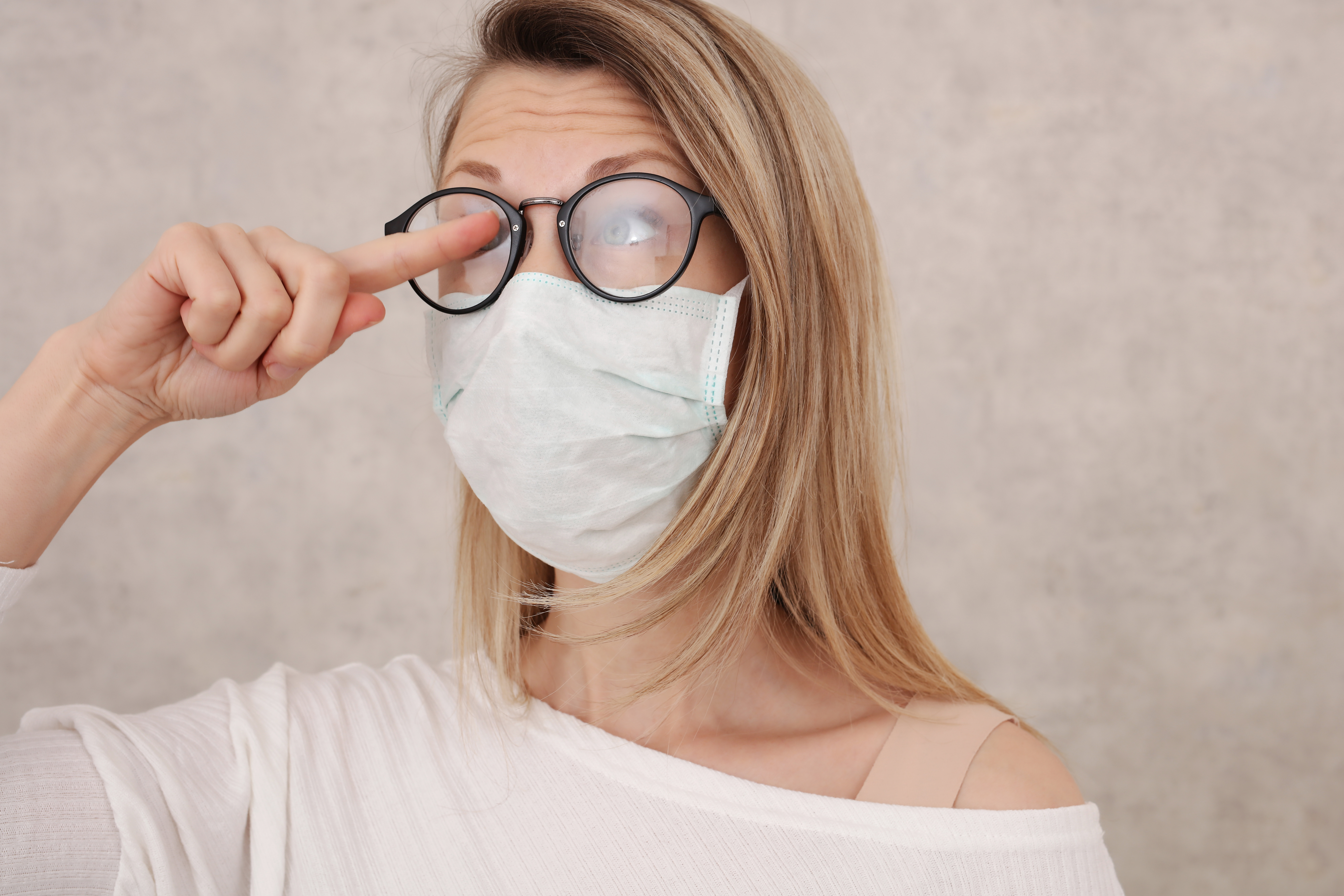 woman wearing glasses and a face mask trying to un-fog them